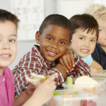 Group Of Elementary Age Schoolchildren Eating Healthy Packed Lun