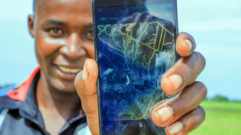 Tanzanian man holding a mobile phone